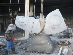 Heavy duty cranes and slings used to position the sculpture on the base